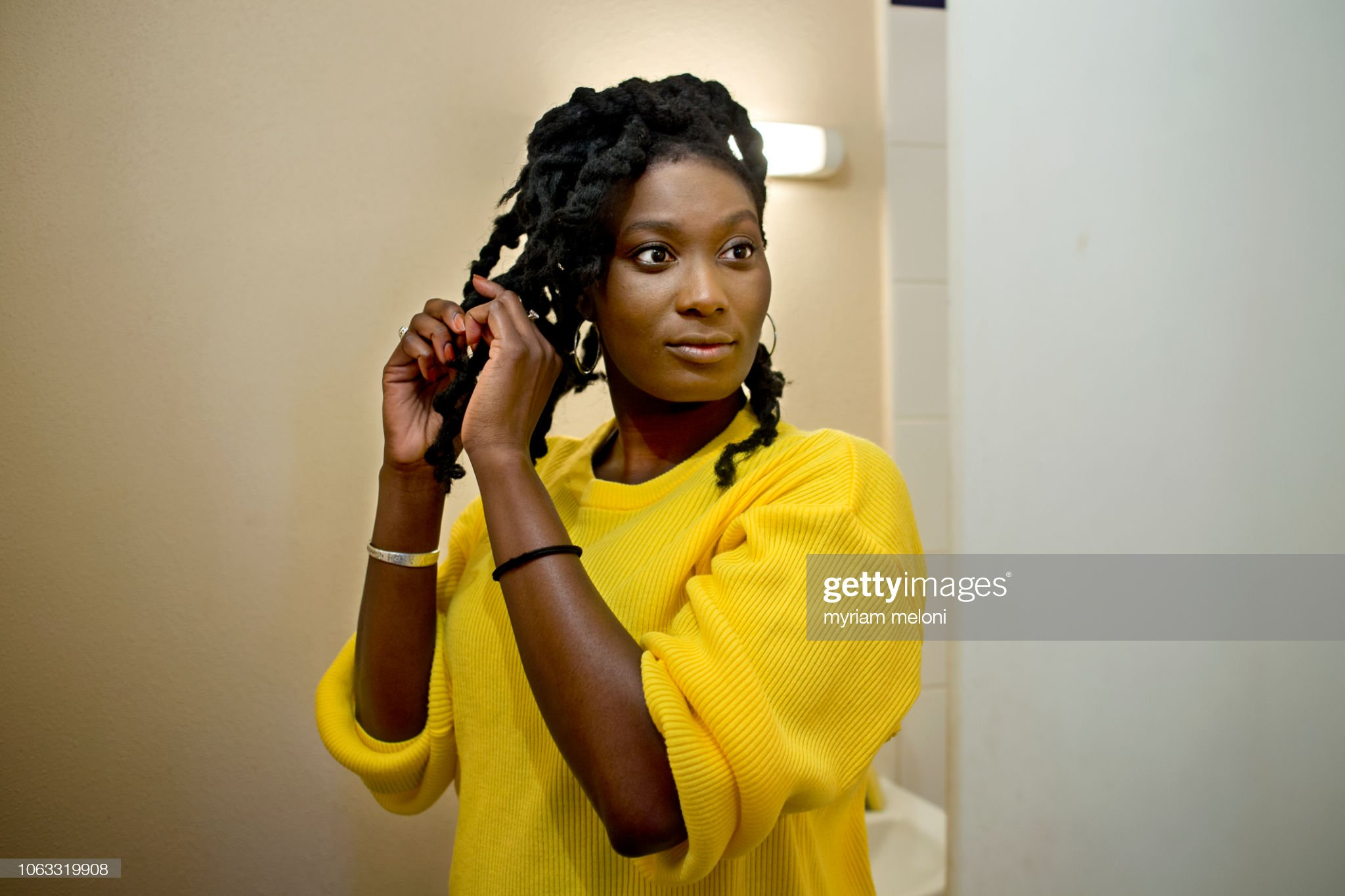 Young black woman doing herself a hairstyle : Stock Photo
