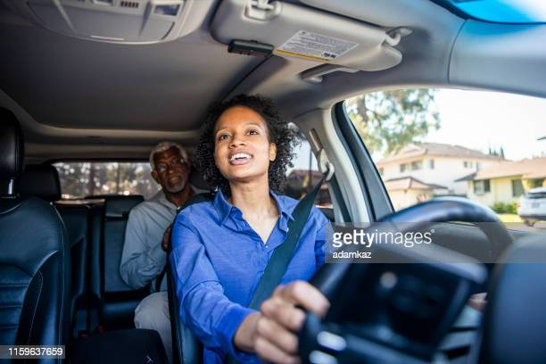 young black woman driving car for rideshare - passenger stock pictures, royalty-free photos & images