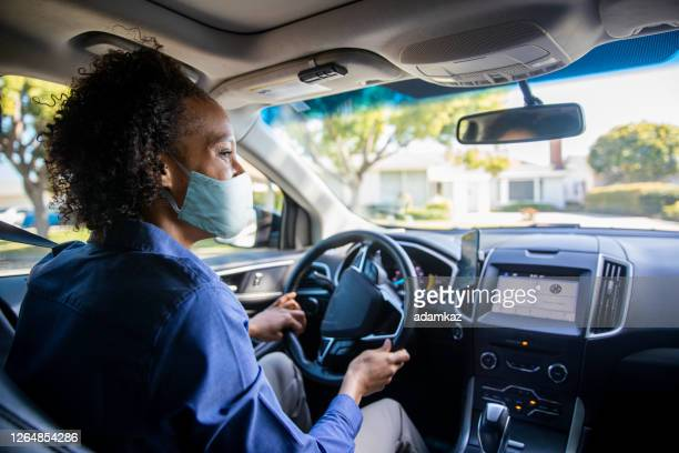 young black woman driving car for rideshare wearing a mask - adamkaz stock pictures, royalty-free photos & images