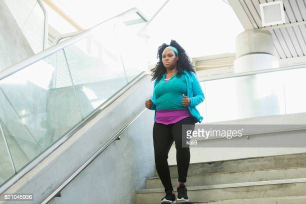 Young black woman exercising, running down steps