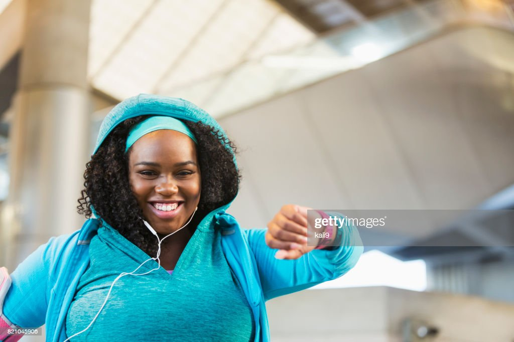 Young black woman exercising, using fitness tracker : Stock Photo