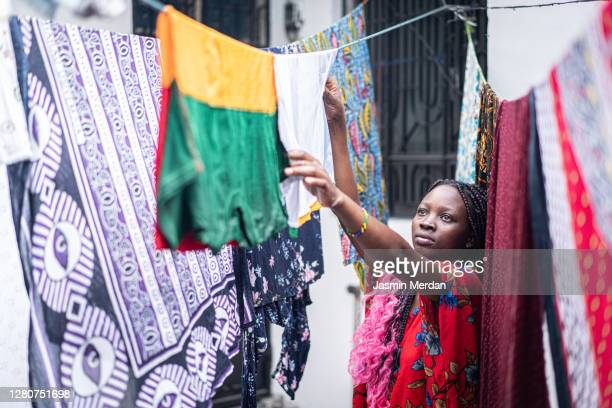 young black woman hanging laundry - clothing stock pictures, royalty-free photos & images