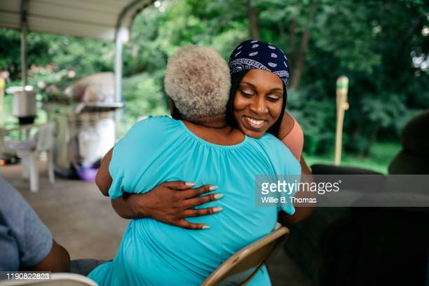 young black woman hugging senior family member - women stock pictures, royalty-free photos & images