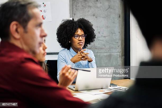 A young black woman in a business meeting.