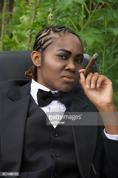 young black woman in male drag, examining viewer critically. - black transvestite stock pictures, royalty-free photos & images