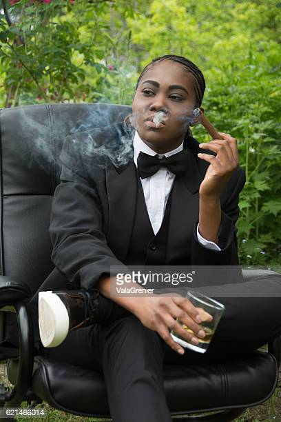 Young black woman in male drag, serious,smoking a cigar.