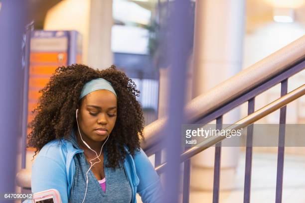 Jeune femme noire dans les vêtements d'entraînement avec écouteurs