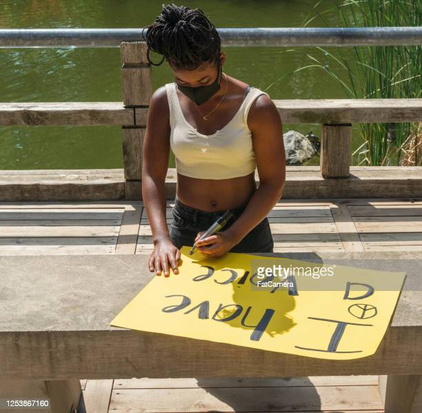 young black woman makes protest sign - anti racism stock pictures, royalty-free photos & images