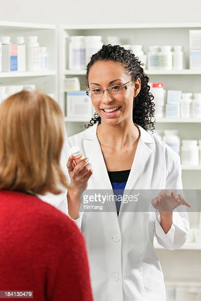 Young Black Woman Pharmacist with Customer in Pharmacy Drug Store