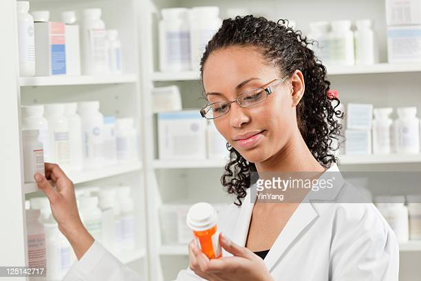 Young Black Woman Pharmacist Working with Prescription Medication in Pharmacy