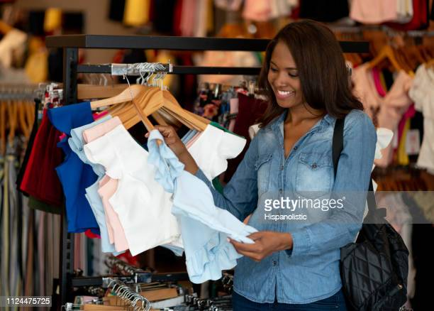 young black woman shopping for clothes at a women's boutique smiling - hispanolistic stock photos and pictures