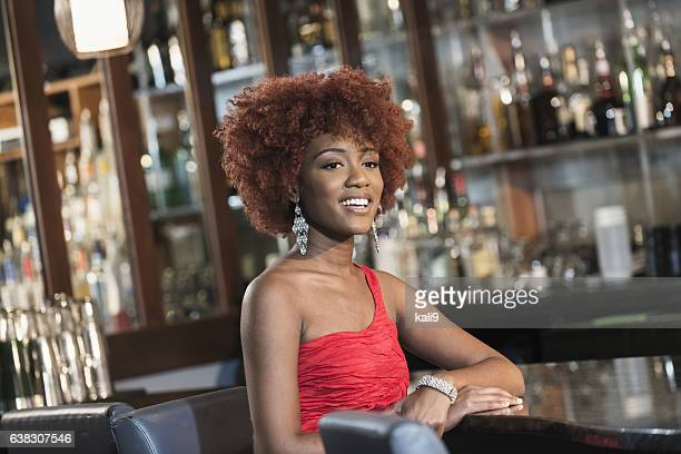 Young black woman sitting at bar in red dress
