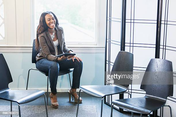 Young black woman sitting by empty chairs, laughing