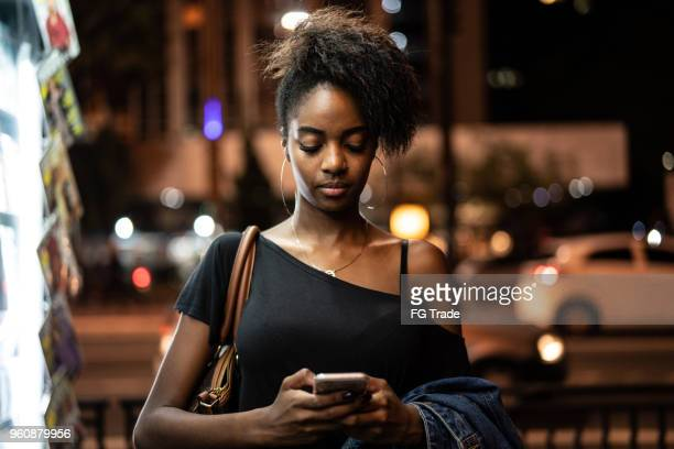 young black woman using mobile in the city at night - nigeria stock pictures, royalty-free photos & images