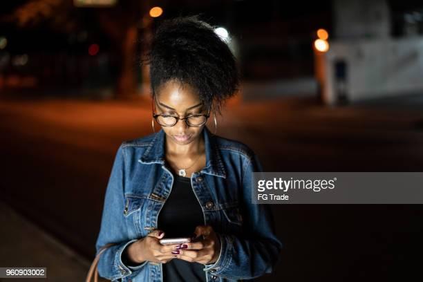 jeune femme noire à l'aide de mobile dans la ville pendant la nuit - nigeria photos et images de collection