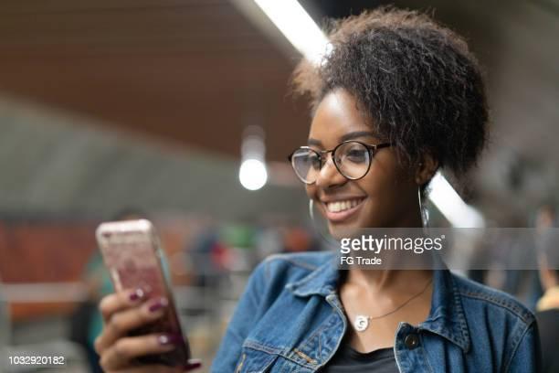 jonge zwarte vrouw met behulp van mobiele in de metro - mobile stockfoto's en -beelden