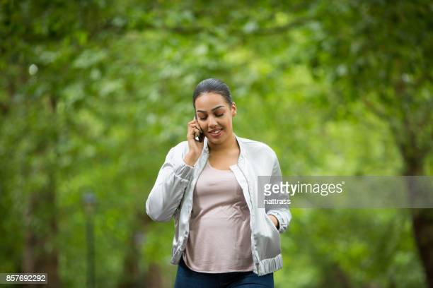 Young black woman walking in the park on her mobile phone