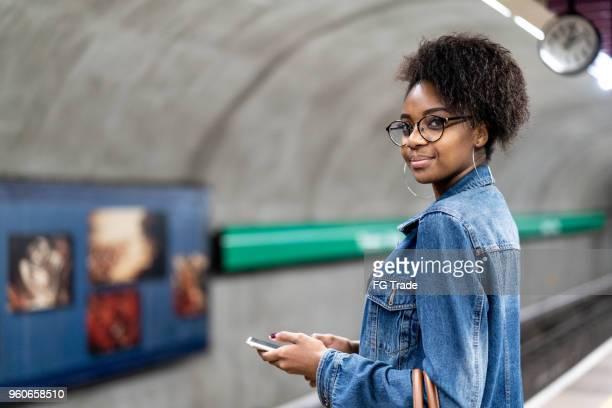 Junge schwarze Frau mit Afro-Frisur mit mobile in der u-Bahn