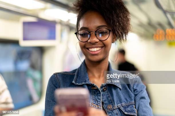 Jonge zwarte vrouw met afro kapsel met behulp van mobiele in de metro