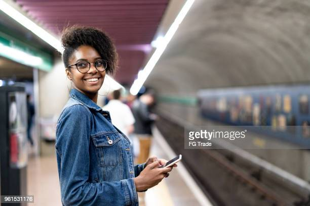 young black woman with afro hairstyle using mobile in the subway - brasil stock pictures, royalty-free photos & images