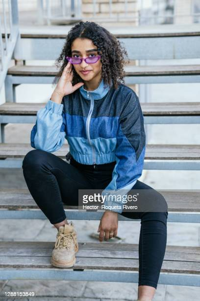 young black woman with violet glasses and blue jacket sitting on the street with happiness expression - coat photos et images de collection