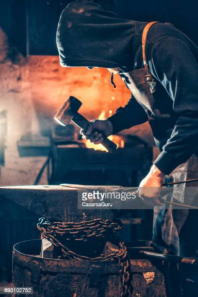 Young Blacksmith Shaping Glowing Knife Iron Blade On Anvil