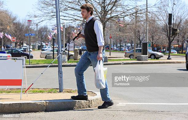 Young blind man walking in his neighborhood after shopping