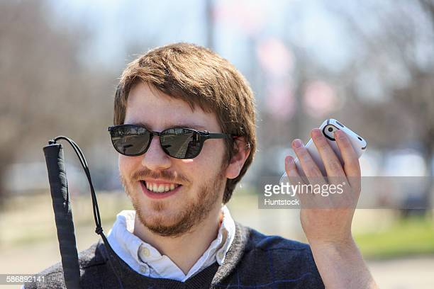 young blind man with cane using assistive technology in his neighborhood - assistive technology stock photos and pictures