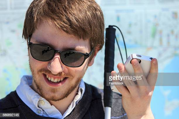 young blind man with cane using assistive technology - assistive technology stock photos and pictures