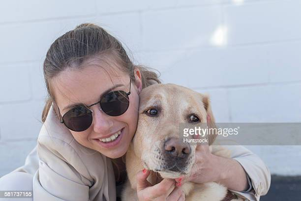 Young blind woman hugging her service dog