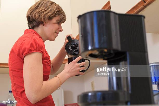 Young blind woman making coffee in her kitchen