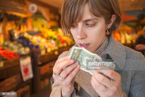 young blind woman pulling out money to pay in a grocery store - 視覚障害 ストックフォトと画像