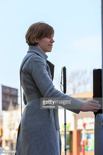 Young blind woman pushing the button to cross the street