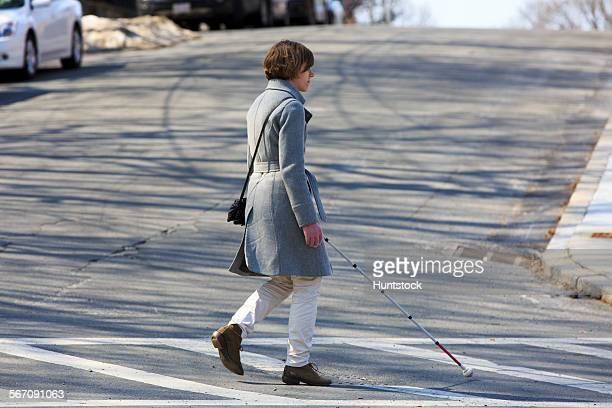 young blind woman using her cane to cross the street - 白杖 ストックフォトと画像