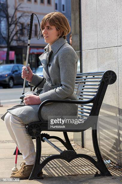 Young blind woman with her cane sitting on a town bench