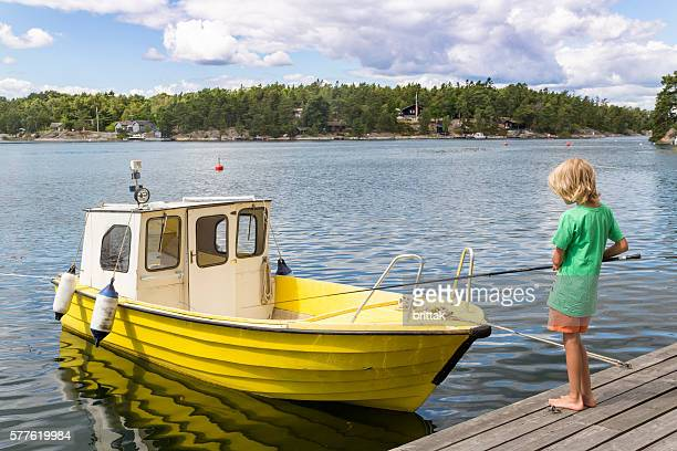 Young, blod fishing boy and yellow boat, Stockhoöm Archipelago, Sweden.