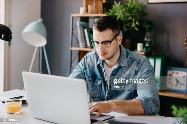 Young blogger working on the laptop from his home office