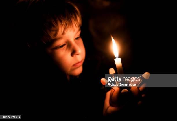 young blond boy holding christingle orange candle, dark background christian advent celebration - candela foto e immagini stock