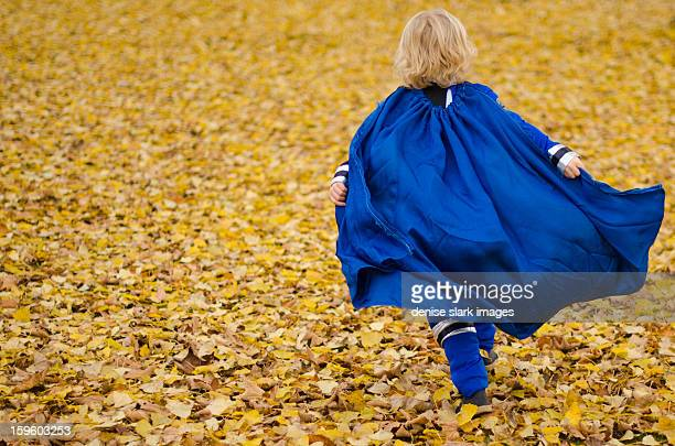 young blond boy running, super hero cape flying