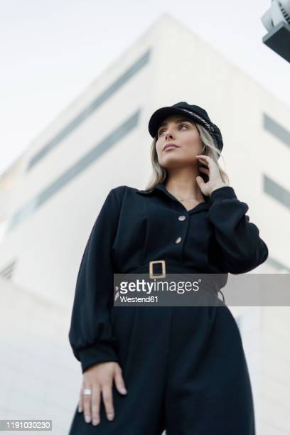 young blond businesswoman wearing black sailor's cap and looking sideways, low angle view - black jumpsuit stock pictures, royalty-free photos & images