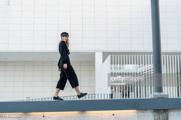 young blond businesswoman wearing black sailor's cap and walking on a wall - black jumpsuit stock pictures, royalty-free photos & images