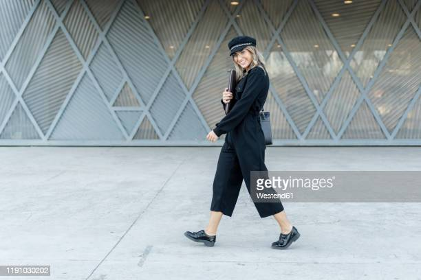 young blond businesswoman wearing black sailor's cap, holding laptop bag, walking and looking at camera - sailor hat stock pictures, royalty-free photos & images
