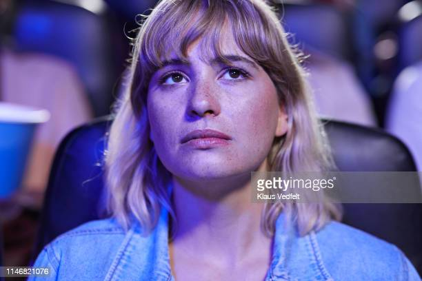 young blond female spectator with blank expression watching movie in theater - braune augen stock-fotos und bilder