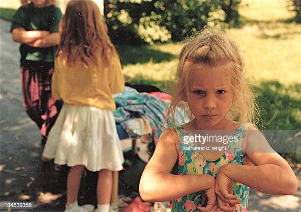 Young blond girl at children's yard sale in summer