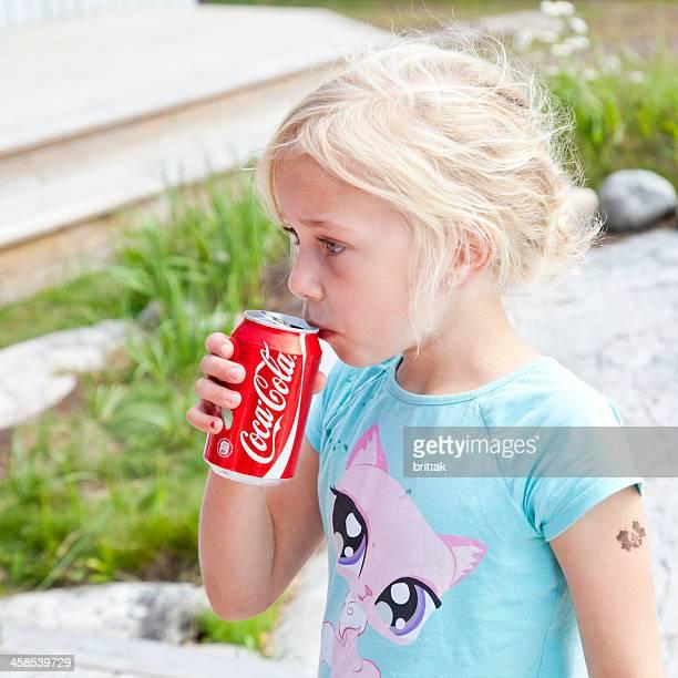 Jeune fille blonde boire de Coca Cola peut en plein air.