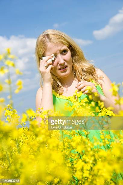 Young blond girl with watery eyes standing in a field of rape