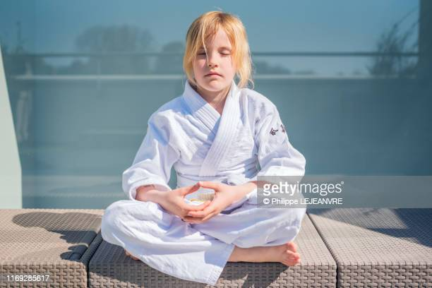 young blond hair girl practising aikido - children only stock pictures, royalty-free photos & images
