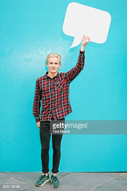 Young blond man holding speech bubble in front of blue wall