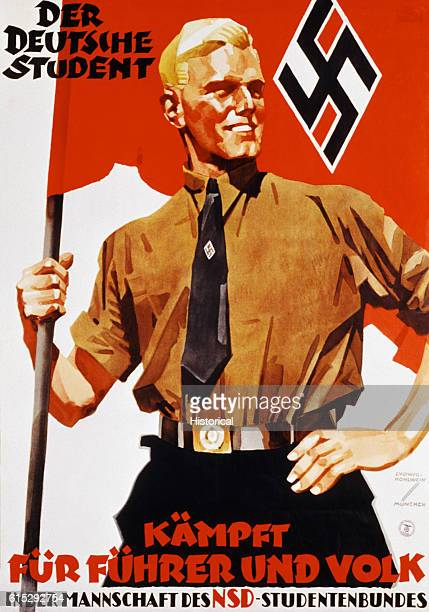 A young blond man wearing a military uniform supports a nazi flag with one hand the other hand on his hip He stands upright and smiles