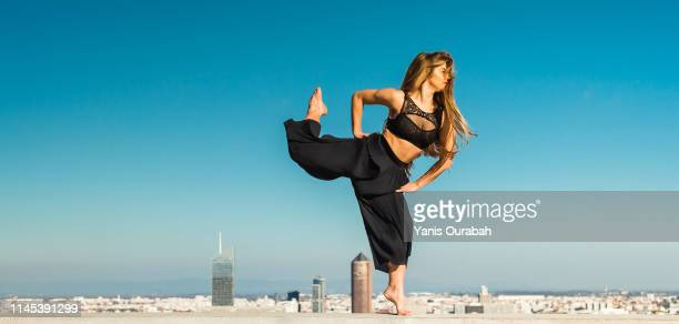 young blond modern dancer dancing in the streets of lyon, france with a panorama of the city in background - solo una donna giovane foto e immagini stock
